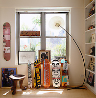 A collection of hand-painted skateboards are displayed against the window in the dining area