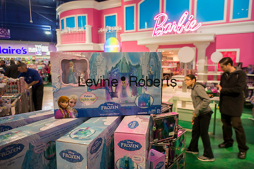Disney's Frozen merchandise is seen in front of the Barbie display at Toys R Us in Times Square in New York on Tuesday, November 25, 2014. According to a recent survey for the first time in eleven years Barbie is not the top pick for girls having been replaced by Anna and Elsa of Frozen.   (© Richard B. Levine)