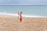 Two year old boy playing with a stick on the beach at Playa Bluff Lodge, Bocas del Toro, Colon Island, Panama