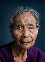 "Mastia (born 1927) was one of tens of thousands of 'comfort women' forced into prostitution by the Japanese military during World War II..Mastia was taken from home by soldiers along with 15 other girls and transported to barracks in Cimahi. While the others were forced into prostitution, a Japanese captain picked her from the group and commandeered her as his private comfort woman. For half a year, she lived as a forced concubine in his quarters, an Indonesian military aid standing guard at her door. When the captain was reassigned, she had to accompany him. This way she stayed in several barracks until the end of the war. After returning home, she went through a religious cleansing ceremony to wash away the 'sin'. ""People nevertheless continued to call me a 'Japanese hand-me-down'. That made me very sad. I still think about it often."" She has been married four times. ""I was very much in love, but after a few years the marriages often failed because we didn't like each other all that much anymore. With the last man I was married 25 years, but he took on another woman because I couldn't have any children."" Since her husband's death she lives by herself and still works in the rice fields.."
