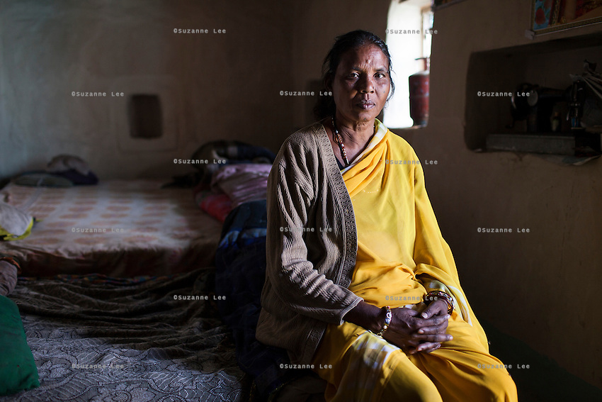 Community reporter Shanti Adivasi, 52, sits for a portrait in her house, bought with the income she made from being a journalist, in Manikpur, Chitrakoot, Uttar Pradesh, India on 6th December 2012. Shanti used to be a wood gatherer, working with her parents since she was 3, and later carrying up to 100 kg of wood walking 12km from the dry jungle hills to her home to repack the wood which sold for 3 rupees per kg. After learning to read and write in an 8 month welfare course, at age 32, she became a reporter, joining Khabar Lahariya newspaper since its establishment in 2002, and making about 9000 rupees per month, supporting her family of 14 as the sole breadwinner. Photo by Suzanne Lee for Marie Claire France.