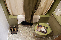 Waders, wading boots and a fishing catalog in the bathroom of a small motel during a fishing road trip to the Driftless Area of Southwest Wisconsin.