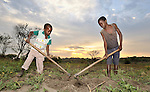 Robert Mana (9), left, and his brother Manaseh Banja (12), work their family's small agricultural plot as the sun rises in the Southern Sudan village of Ligitolo. Families here are rebuilding their lives after returning from refuge in Uganda in 2006 following the 2005 Comprehensive Peace Agreement between the north and south. These two boys are sons of the village's United Methodist pastor. NOTE: In July 2011, Southern Sudan became the independent country of South Sudan