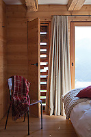 The walls of the contemporary bedroom have been lined in wood, a tall window protected on the outside by rough slats of wood which filter the light