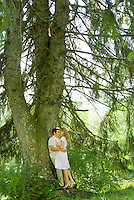 Couple in embrace leaning against tree