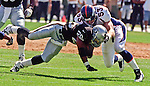 Oakland Raiders vs. Denver Broncos at Oakland Alameda County Coliseum Sunday, September 20, 1998.  Broncos beat Raiders  34-17.  Denver Broncos linebacker Bill Romanowski (53) knocks Oakland Raiders running back Napoleon Kaufman (26) to the ground.
