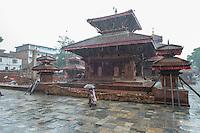 Nepal, Kathmandu, earthquake damage at Kathmandu Durbar Square. Pouring monsoon rain.