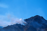 870000357 a los angeles county fire fighting helicopter performs an aerial retardant drop on burning hillside in the path of the topanga fire in the hills above the san fernando valley in southern california