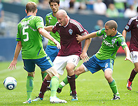 Colorado Rapids forward Conor Casey, center battles Seattle Sounders FC defender Tyson Wahl, left, and midfielder Osvaldo Alonso for the ball during play at CenturyLink Field in Seattle Saturday July 16, 2011. The Sounders won the game 4-3.