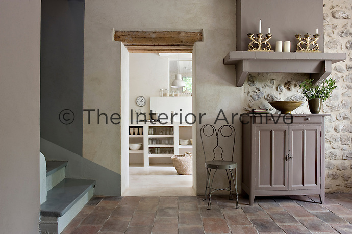 In the entrance hall a massive open shelf is painted the same flat grey as the antique cupboard beneath whilst to one side the kitchen can be seen through a doorless entrance