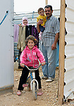 A Syrian family stands in the doorway of their shelter in the Zaatari refugee camp near Mafraq, Jordan. Established in 2012 as Syrian refugees poured across the border, the Zaatari camp held more than 80,000 refugees by 2015, and was rapidly evolving into a permanent settlement. ACT Alliance member agencies provide a variety of services to refugees living in the camp.