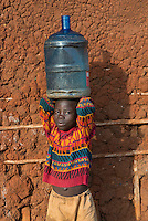 "A boy carries a heavy water jug from the local well at Kakira Sugar Estate Plantation in Jinja District, Uganda, Africa. There is no running water in any of the homes of this poor area where most people work on the affiliated sugar planation. It's often the children who are sent to the well to fetch the water in whatever containers they can find. The well at least affords them clean drinking water, whereas in many other areas locals are reliant on the often unclean rivers or lakes for drinking water. I was photographing for BRAC, a non-profit focused on micro-finance loan projects in developing countries. In this township they were helping children rise above their circumstances through scholarship programs to attend to school. ""The only hope we have,"" one mother told me, ""is for our children to attend school and have a better life than we have."""