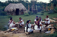 Maya women cooking tortillas over open fires. Traditional Mayan house or Na in background. Yucatan, Mexico.