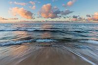 Sunset colors softly reflect over a beach in Waialua, North Shore, O'ahu.