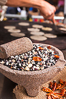 Hard blue and yellow corn and dried chilis on a stone mortar with pestle, before it is ground into corn meal for tortillas.