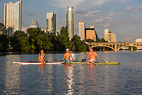 Austin surfers sit on stand up paddle boards and huddle in the middle of Lady Bird Lake with the Austin skyline in the background on a sizzling summer's day.