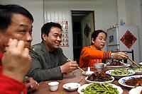 Li Fang (gauche), Li Daquan (centre) et Qiang Yun (droite) partagent le repas du samedi soir dans leur appartement, à Baoshan, près de Shanghai, le 10 mai 2008. Photo par Lucas Schifres/Pictobank