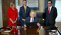 United States President Donald J. Trump looks over the document prior to signing the first of three Executive Order concerning financial services at the Department of the Treasury in Washington, DC on April 21, 2017.  From left to right: US Representative Claudia Tenney (Republican of New York) US Senator David Perdue (Republican of Georgia), the President, and US Secretary of the Treasury Steven Mnuchin.<br /> Credit: Ron Sachs / Pool via CNP /MediaPunch