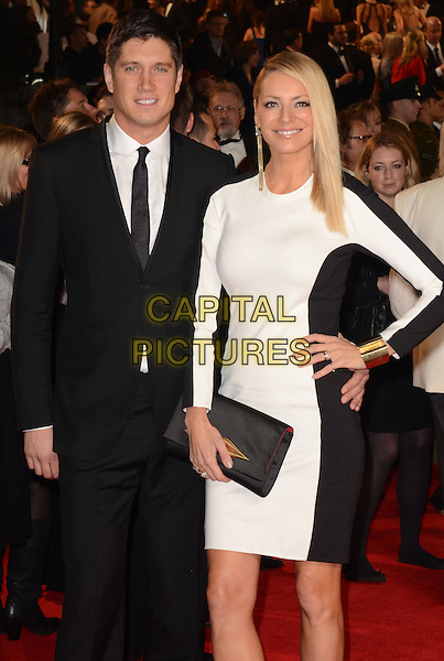 Vernon Kay and Tess Daly.Royal World Premiere of 'Skyfall' held at the Royal Albert Hall, London, England..October 23rd, 2012.half 3/4 length black white dress clutch bag hand on hip suit married husband wife .CAP/WIZ.© Wizard/Capital Pictures.