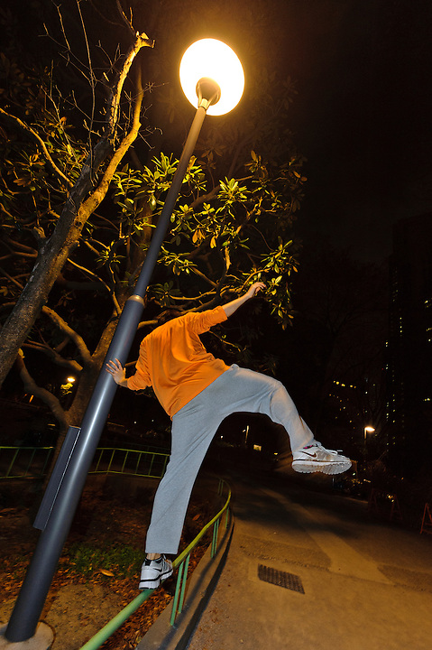 Balancing on a park rail. Parkour Tokyo group practice, Shinjuku Chuo Koen, Tokyo, Japan, January 10, 2012. Parkour is a modern method of physical training, also known as freerunning. It was founded in France in the 1990s. There is a small group of around 50 parkour practitioners in Tokyo.