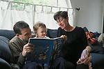 """Berkeley, CA Parents enjoying """"The Cat in the Hat"""" with daughter twenty months old, mother pregnant, holding child's baby doll MR"""