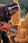 Woodcarver using chainsaw to carve sculpture of elf