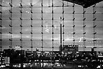 The glass front of the main railway station in Berlin with view of the skyline in the evening.