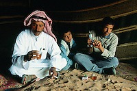 "Jordan. Wadi Rum.The Wadi Rum is a large, beautiful and deserted area where bedouins live under tents. Man dressed in traditionnal bedouin clothes - long white dress                      "" djellaba"" and a turban on the head - seat on the sandy ground in the tent and drink tea. A teenage boy wears western clothes and plays with a plastic gun in his hands. The man works as a tourist guide.  © 2002 Didier Ruef"