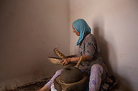 Morocco - Tidzi - Amina Hammoush, 40, shakes the roasted nuts to remove the impurities before putting it into the traditional grinder.