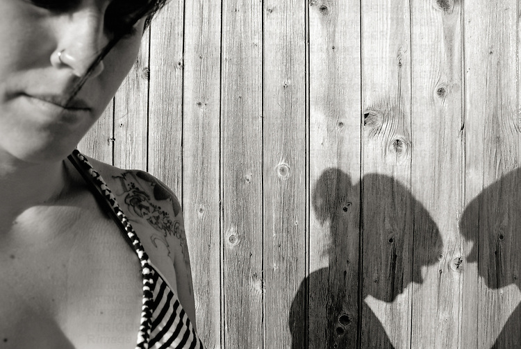 young woman passing a wooden wall meeting two shadows