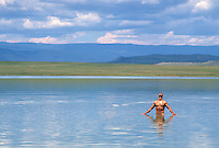 naked man soaking in the sun while standing in a lake in New Mexico