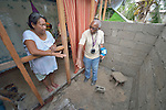 Sonia Sacorate talks with Leopold Sindayigaya, a water and sanitation advisor for Norwegian Church Aid, in what will become her bathroom in Bacubac, a seaside neighborhood in Basey in the Philippines province of Samar that was hit hard by Typhoon Haiyan in November 2013. The storm was known locally as Yolanda. Norwegian Church Aid, a member of the ACT Alliance, is sponsoring the construction of bathrooms with septic systems for houses in the village where existing systems were destroyed by the typhoon's unusually high storm surge.