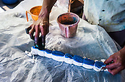 Workers seen mixing colours and dyeing fabric at a batik workshop in Jaipur, Rajasthan, India.