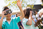 Alex and Jessica Borrillo test out goofy glasses during an exhibit in Los Altos hosted by The Exploratorium museum Aug. 11.