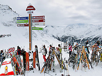"Switzerland. Canton Valais. Ski tourists in Verbier at  "" La Chaux"" ( 2260 meters ). Verbier is a village located in the municipality of Bagnes in the Val de Bagnes. Verbier is one of the largest holiday resort and ski areas in the Swiss Alps. Ski poles and skis in the snow. Rivella advertising. Indication signs. 3.01.2012 © 2012 Didier Ruef"