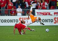 01 July 2010:  Houston Dynamo midfielder Danny Cruz #5 tumbles over Toronto FC defender Nick Garcia #4 during a game between the Houston Dynamo and the Toronto FC at BMO Field in Toronto..Final score was 1-1....