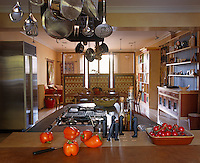 General view of a contemporary kitchen over a central island with pans hanging on a frame from the ceiling