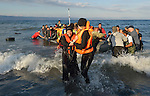 Helped by a volunteer, a refugee woman disembarks from a rubber raft onto a beach near Molyvos, on the Greek island of Lesbos, on October 30, 2015. She and the other refugees crossed the Aegean Sea from Turkey and were received by local and international volunteers. They then proceeded on their way toward western Europe. The boat was provided by Turkish traffickers to whom the refugees paid huge sums to arrive in Greece.