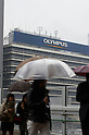 November 11, 2011, Tokyo, Japan - Against the backdrop of Olympus billboard, pedestrians scurry by in the cold mid-autumn rain in Tokyos Shinjuku on Friday, November 11, 2011. As is the weather, bleak is the companys future...The admission of the worlds biggest maker of endoscopes that it has hidden securities losses may lead to its delisting by the Tokyo Stock Exchange as Japanese police have reportedly launched a full investigation into the companys concealment dating back to the 1980s. Olympus said its likely to miss November 14 deadline for releasing its first-half earnings, prompting the TSE to place the Tokyo-based company on a watch list for a review for possible delisting. Olympus shares have lost around 80 per cent of their value since the scandal broke on October 14 when the company ousted British CEO Michael Woodford, who alleged overpayments in the acquisition deals. (Photo by Yutaka/AFLO) [1040] -mis-