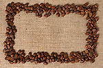 Horizontal frame made from aromatic coffee beans on sacking fabric background.