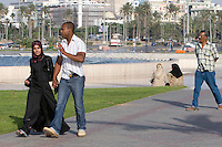 Tripoli, Libya, North Africa - Interracial Couple at Public Park near the Green Square, downtown Tripoli.  Both wear typical dress for contemporary Libyans--a scarf covers the head of the woman, who wears an ankle-length abaya.  The man wears casual European or western clothes, levis and a short-sleeved shirt.  Holding Hands.