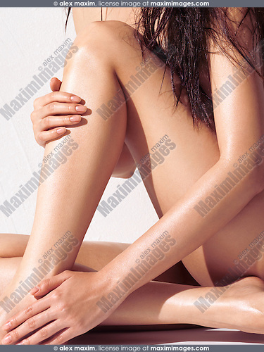 Sensual artistic closeup of a young woman bare legs and hands with shiny skin and wet hair