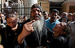 An Egyptian Coptic Christian cleric consoles relatives of the victims of sectarian violence and denounces sectarian tensions October 10, 20011 at the Coptic Hospital in Cairo, Egypt. At least 26 people, mostly Christian, were killed during sectarian clashes that saw the worst violence since the Revolution that toppled former Egyptian president Hosni Mubarak earlier this year. Egyptian Coptic Christians make up about 10% of Egypt's 80 million population and periodically violence flares between the Christian minority and the majority Muslim population. (Photo by Scott Nelson)