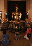 Visitors pay homage to the golden image of Buddha in Bangkok, Thailand. The great Buddha, a solid five and a half ton gold, statue cast 700 years ago, vanished from its dias during an invasion by the Burmese. In 1955, a heavy but nondescript state of Buddha was found in Northern Thailand, When a heavy crane was used to lift it, the crane and hoist broke and the statue fell,. When the outer flesh of cement cracked and the gold glittered, a lost treasure was found. (Jim Bryant Photo).....