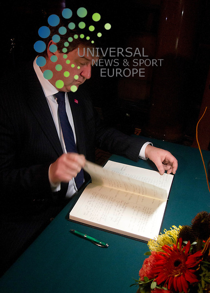 Secretary of State for Scotland Alistair Carmichael signs a book of condolence for the Clutha bar victims at the City Chambers in Glasgow. <br />
