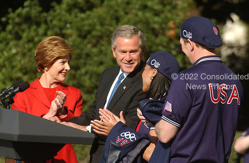 United States President George W. Bush and first lady Laura Bush make remarks to the 2004 United States Olympic and Paralympic teams on the South Lawn of the White House in Washington, D.C. on October 18, 2004.  Left to right: First lady Laura Bush; President Bush; Dawn Staley, Olympic basketball player; and Kevin Szott, paralympic Judo competitor.<br /> Credit: Ron Sachs / CNP