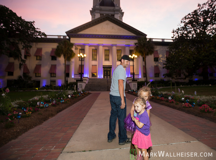 Seth Beckstead, top, watches 4 year old Remi Pagean, partially hidden playing with her 2 year old sister and cystic fibrosis carrier Shiloh Pagean during the Light Up CF event by the Cystic Fibrosis Lifestyle Foundation at the Florida Capitol in Tallahassee, Florida.