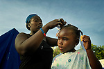 Monique Izidor braids the hair of her neighbor's daughter, Gengy Badis, as the girl prepares for school in a camp in Grand-Goave, Haiti, where families left homeless by the January 2010 earthquake continue to live. The ACT Alliance has supported families in this camp with a variety of services, and has rebuilt a school beside the tent city.