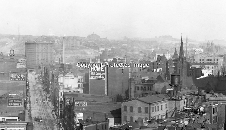 Building Advertising: for the following companies: Lyle Brothers Hardware, Home Trust Company of Pittsburgh, John Wallace Produce, Renwick Brothers Wholesale Millinery, J.C.Lindsay Hardware Company, Monongahela National Bank<br /> <br /> Pittsburgh PA:  View of Liberty Avenue from the top of the Empire Building.  Pennsylvania Railroad's Union Station in background.