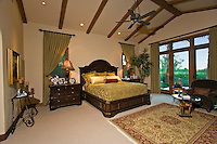 Master bedroom is seen during the day with beautiful textile draperies and oriental rug